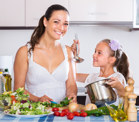 spanish woman: Portrait of spanish woman and little girl cooking vegetables Stock Photo
