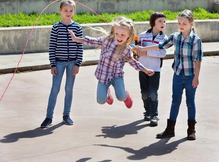 スキップ ロープ ジャンプ ゲーム、屋外に笑って遊んでいる子供たち 写真素材