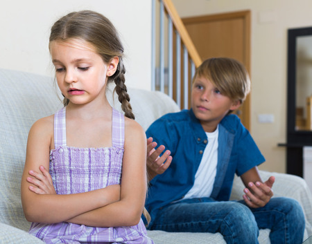 berate: Teenage american boy and sad little girl quarrelling at home. focus on girl