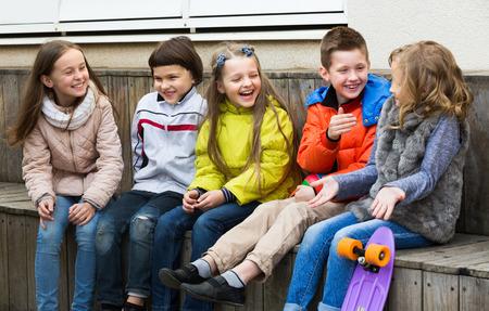 Gelukkige jongens en meisjes die geheimen delen als praten outdoor