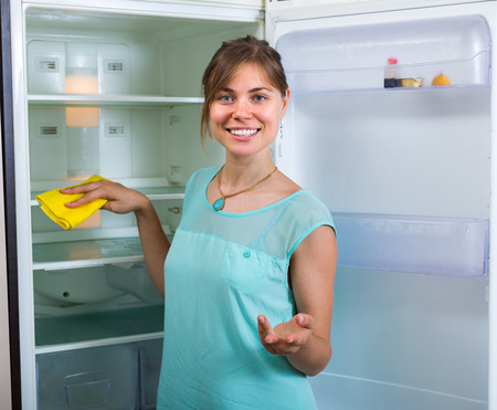 handglove: Smiling girl wiping fridge parts with lint-free rag