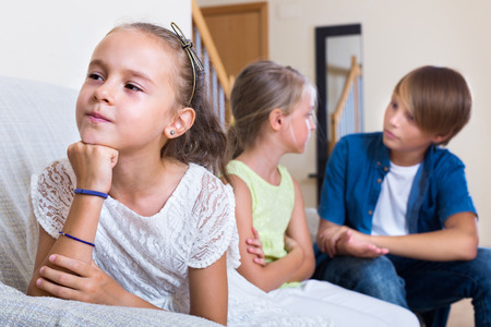 envy: Envy little child sitting aside of boy and girl at home Stock Photo