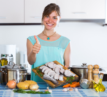 householder: Cheerful young smiling woman cooking sliced fish at home kitchen Stock Photo