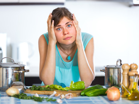 reluctance: Portrait of exhausted young woman at home kitchen