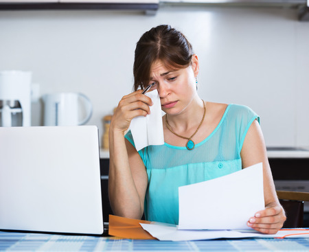 downcast: Unhappy housewife reading banking statement in the kitchen
