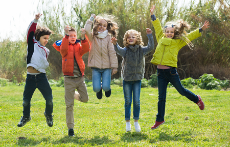 high spirits: Group of children in high spirits jumping outdoors Stock Photo
