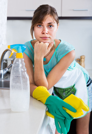 unwillingness: Tired young woman in a rubber gloves posing at kitchen Stock Photo