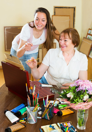 the elderly tutor: Smiling mentor assesses the work of his mature student Stock Photo