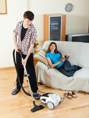 get tired: Young man cleaning with vacuum cleaner while wife lying with eBook