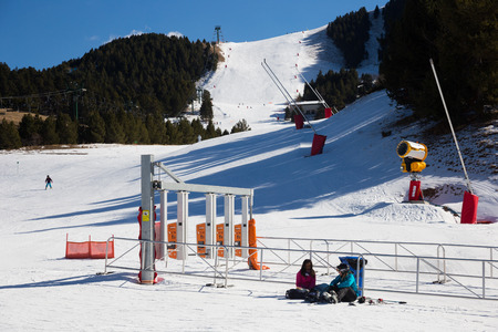 GIRONA, SPAIN - FEBRUARY 19, 2016: Group of fully equipped skiers go down the piste, marked ski run, at La Molina ski resort in Pyrenees mountains
