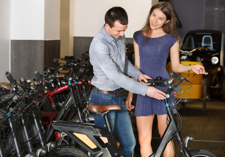 rental agency: Happy young couple selecting bikes at rental agency indoors. Focus on women Stock Photo