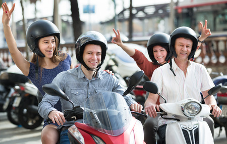 youthfulness: Young and mature couples driving petrol scooters outside and smiling. Focus on young man Stock Photo