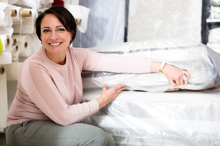 matress: Happy brunette choosing sleeping mattress in textile shop Stock Photo