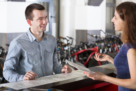 rental agency: Happy young couple selecting bikes in the rental agency indoors. Focus on man