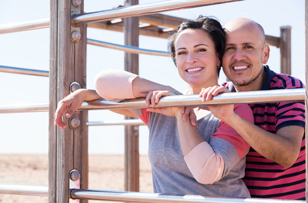 wall bars: Portrait of happy man and woman standing together close to wall bars and smiling