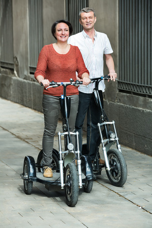 staying: Mature couple staying with electric bikes outside and smiling. Focus on both persons Stock Photo