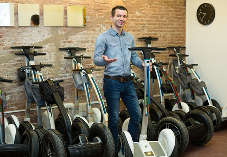 rental agency: Positive male consultant in front of segways at rental agency Stock Photo