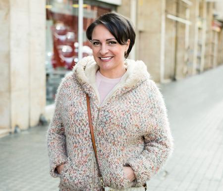 outerwear: Portrait of positive brunette in outerwear on city street Stock Photo