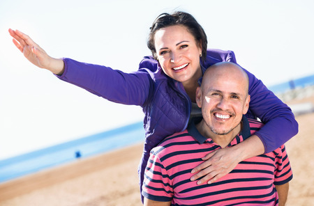 gladly: Cheerful  charming mature couple gladly hugging each other and enjoying the beach