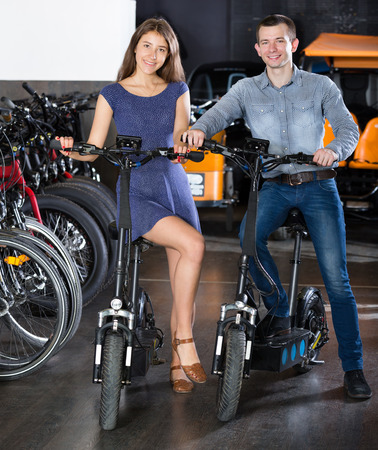 rental agency: Happy young couple selecting the bikes in rental agency indoors. Focus on both persons Stock Photo