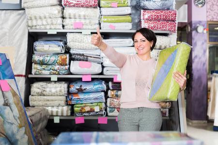 bedspread: Happy mature customer handles bedspread near textiles shelves inside