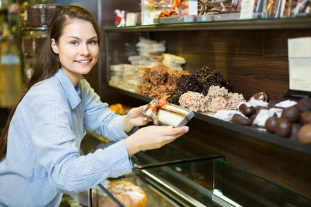 shopgirl: Adult brunette girl buying dark and white chocolate with fillings