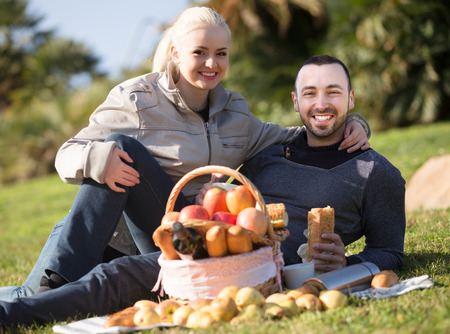 lounging: Smiling couple lounging in sunny spring day at picnic outdoors Stock Photo