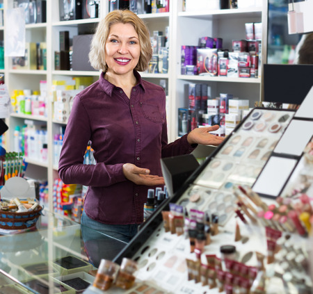 beauty store: Mature female seller near display with cosmetics in beauty store