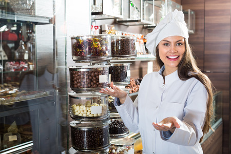 shopgirl: Cheerful smiling young shopgirl posing with different chocolate and confectionery at display