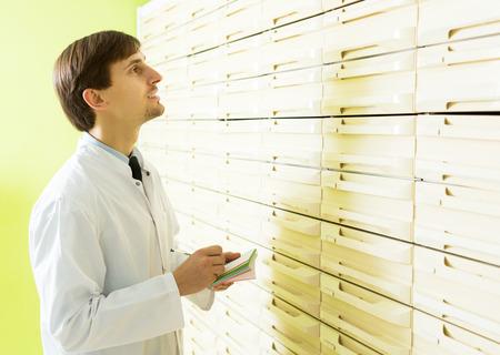 depot: Smiling male pharmacist posing in pharmacy depot