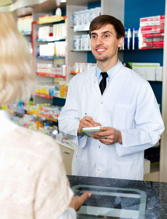 farmacy: Experienced friendly  pharmacist counseling female customer in modern farmacy