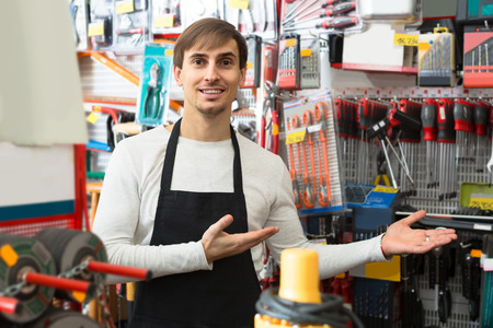 tooling: positive male seller posing at tooling section of household store Stock Photo