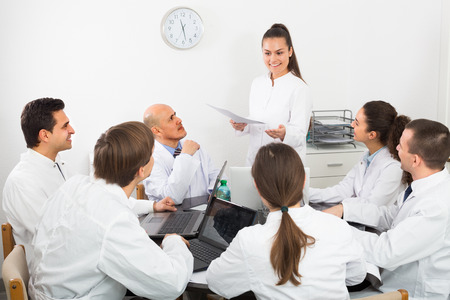 physiotherapists: employees in white overalls having discussion of research work
