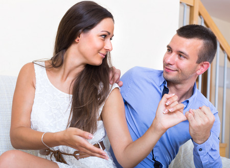 easing: Young couple happily reconciling after quarrel at home. Focus on guy