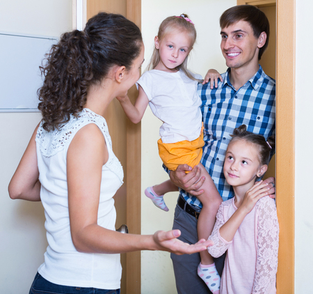 recieving: happy spanish adults and kids meeting at doorway and greeting one another