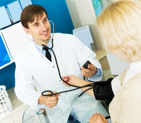 sphygmomanometer: Smiling pharmaceutist taking  mature woman blood pressure using sphygmomanometer in pharmacy Stock Photo