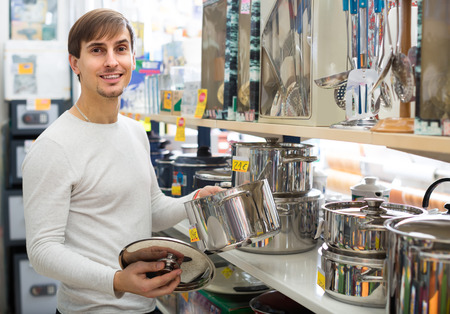 stockpot: Young man choosing stockpot in household store and smiling