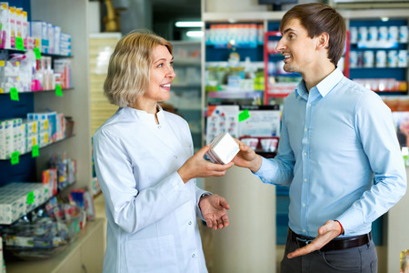 farmacy: Experienced female pharmacist counseling customer about drugs usage in modern farmacy Stock Photo