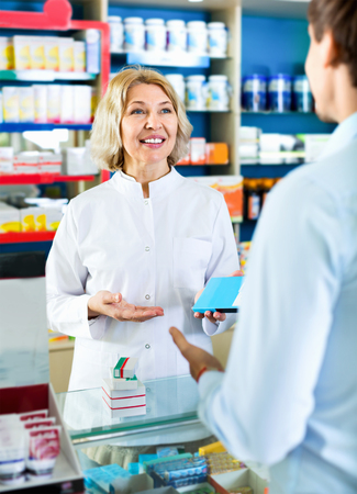 farmacy: Friendly female pharmacist counseling customer about drugs usage in modern farmacy Stock Photo