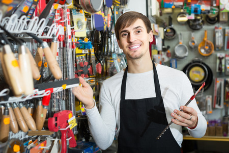 tooling: Young russian male seller posing at tooling section of household store