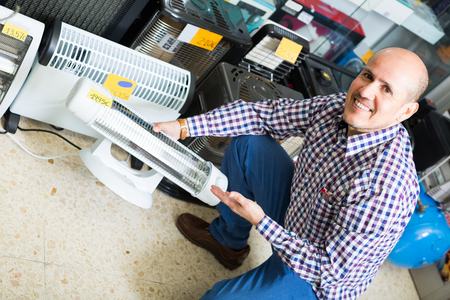 radiative: Ordinary senior man choosing electric heater in household store