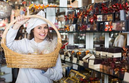 shopgirl: Smiling european shopgirl posing with delicious ganaches, praline and chocolates
