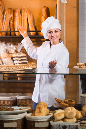 shopgirl: Happy shopgirl working in bakery with bread and pastry Stock Photo