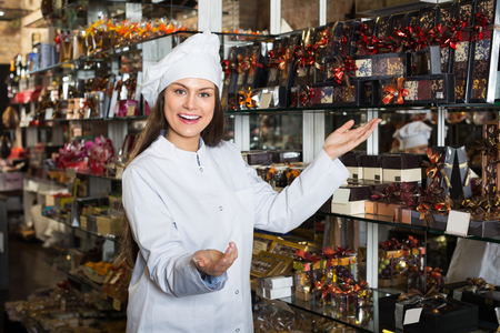 shopgirl: Positive woman selling fine chocolates and confectionery in cafe Stock Photo
