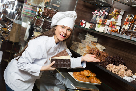 shopgirl: Cheerful  smiling young shopgirl posing with delicious chocolate and confectionery at display