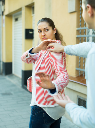 accosting: Young couple having bad quarrel on city street Stock Photo
