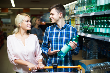 sparkling water: Young happy customers choosing bottle of sparkling water at supermarket