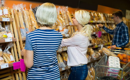 ordinary: Ordinary customers choosing fresh baked bread and pastry in supermarket