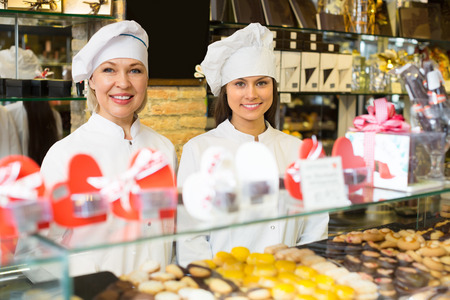 saleswomen: Happy saleswomen with delicious chocolate and confectionery at display . Selective focus