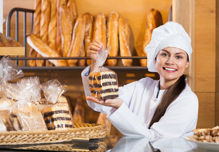 shopgirl: Portrait of friendly smiling charming woman at bakery display with pastry